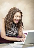 Modelo femenino usando la computadora portátil Foto de archivo libre de regalías