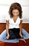 Modelo femenino usando la computadora portátil Imagen de archivo