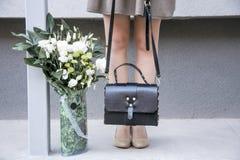 Modelo Girl de la belleza con las flores y bolso en gris imagen de archivo libre de regalías