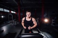 Modelo grande fuerte joven de la aptitud del hombre en el gimnasio que corre en la rueda de ardilla con la botella de agua Foto de archivo libre de regalías