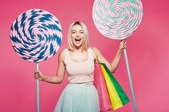 Modelo hermoso con los dulces en el fondo rosado imagen de archivo libre de regalías