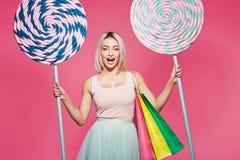 Modelo hermoso con los dulces en el fondo rosado imagen de archivo