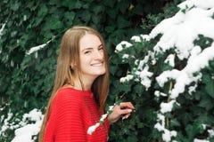 Modelo hermoso de la chica joven en invierno en un parque parqueado en un suéter rojo Foto de archivo libre de regalías
