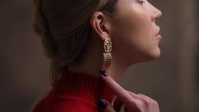 Modelo hermoso de la moda en el vestido rojo que presenta con los pendientes almacen de video