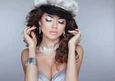 Modelo hermoso de la muchacha con maquillaje, pelo rizado y el pendiente de la moda Foto de archivo libre de regalías