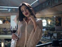Modelo hermoso de la muchacha que plantea la situación con un vidrio de vino tinto en su mano en un restaurante fotografía de archivo libre de regalías