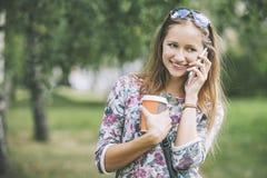 Modelo hermoso de la mujer con café para llevar y un teléfono Imágenes de archivo libres de regalías