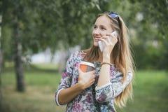 Modelo hermoso de la mujer con café para llevar y un teléfono Fotografía de archivo libre de regalías