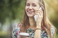 Modelo hermoso de la mujer con café para llevar y un teléfono en t Foto de archivo libre de regalías