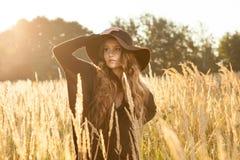 Modelo hermoso de la señora joven en campo en la puesta del sol Foto de archivo libre de regalías