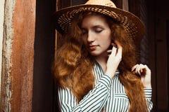 Modelo hermoso del pelirrojo con los ojos cerrados en el sombrero de paja que presenta adentro Imagenes de archivo