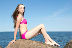 Modelo hermoso en el bikini rosado que se sienta en piedra en la playa rocosa Fotos de archivo libres de regalías