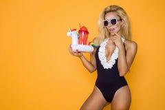Modelo hermoso en un bikini y gafas de sol, llevando a cabo una bebida y un unicornio inflable imagenes de archivo