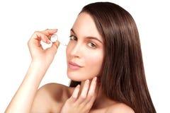 Modelo hermoso que aplica un tratamiento cosmético del suero de la piel imagenes de archivo