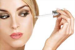 Modelo hermoso que aplica un tratamiento del suero de la piel Fotografía de archivo