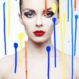 Modelo hermoso a través del vidrio con colores brillantes Foto de archivo