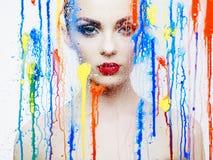 Modelo hermoso a través del vidrio con colores brillantes Imagen de archivo