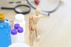 Modelo humano de madeira, álcool de fricção e equipamento médico na tabela imagens de stock royalty free