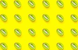 Modelo inconsútil del kiwi partido en dos jugoso maduro en fondo amarillo Endecha minimalista creativa del plano Dieta sana del v fotos de archivo