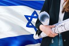 Modelo israelí de la tenencia de la mujer del arquitecto contra fondo de la bandera de Israel que agita Concepto de la construcci foto de archivo libre de regalías