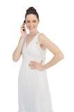 Modelo joven alegre en el vestido blanco que tiene llamada de teléfono Fotos de archivo