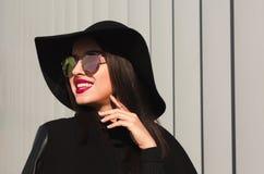 Modelo joven feliz en vidrios del espejo y la presentación brimmed amplia del sombrero fotografía de archivo libre de regalías