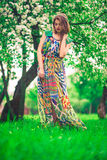 Modelo joven hermoso atractivo en vestido colorido en jardín del verano Imagenes de archivo