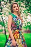 Modelo joven hermoso atractivo en vestido colorido en jardín del verano Fotografía de archivo