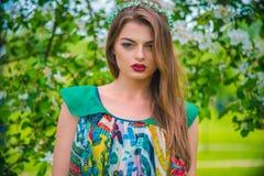 Modelo joven hermoso atractivo en vestido colorido en jardín del verano Foto de archivo libre de regalías
