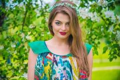 Modelo joven hermoso atractivo en vestido colorido en jardín del verano Imágenes de archivo libres de regalías