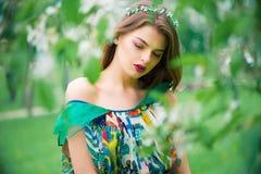 Modelo joven hermoso atractivo en vestido colorido en jardín del verano Imagen de archivo