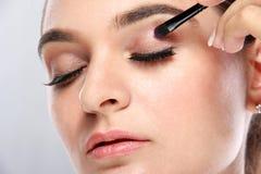 Modelo joven hermoso que aplica un poco de sombreador de ojos Fotos de archivo libres de regalías