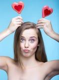 Modelo juguetón hermoso con las piruletas en la forma de un corazón Imagenes de archivo