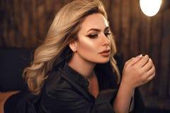 Modelo lindo Retrato louro da mulher na camisa preta Menina elegante com a composição da beleza e o penteado encaracolado que lev imagens de stock royalty free