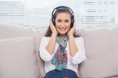 Modelo lindo sonriente que escucha la música Imagen de archivo libre de regalías