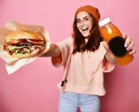 Modelo louro novo bonito de sorriso da mulher no Hamburger da terra arrendada de pano do hoodie do moderno e no suco da garrafa imagem de stock royalty free
