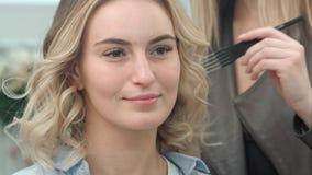 Modelo louro novo que tem o cabelo denominado antes de disparar Imagem de Stock Royalty Free