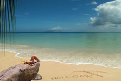 Modelo louro Tanning na praia bem-vinda. Foto de Stock