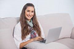Modelo magnífico alegre usando el ordenador portátil que se sienta en el sofá Foto de archivo