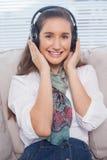 Modelo magnífico sonriente que escucha la música Foto de archivo libre de regalías