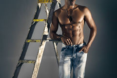 Modelo masculino africano muscular que se inclina contra una escalera en vaqueros Imagen de archivo