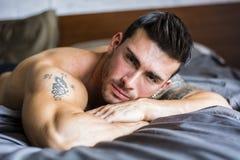 Modelo masculino atractivo descamisado que miente solamente en su cama imagen de archivo libre de regalías