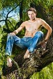 Modelo masculino con las tetas al aire en los pantalones de los pantalones vaqueros que sientan el árbol Fotografía de archivo libre de regalías
