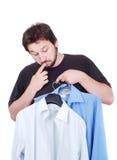 Modelo masculino confuso entre dos camisas imágenes de archivo libres de regalías