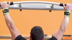 Modelo masculino de la aptitud muscular del atleta que levanta en barra horizontal en un gimnasio metrajes