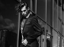 Modelo masculino de la moda hermosa vestido en el traje elegante que plantea el outdooe Metrosexual de pelo largo Cuadro blanco y imagenes de archivo