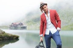 Modelo masculino de la moda que presenta delante de un lago Imagen de archivo libre de regalías