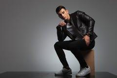 Modelo masculino en la presentación de la chaqueta de cuero asentado mientras que piensa Imagen de archivo