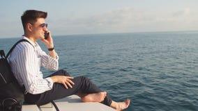 Modelo masculino hermoso que presenta delante de un yate de lujo durante vacaciones de verano almacen de video