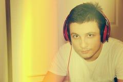 Modelo masculino joven que escucha la música en la cámara en casa Imagenes de archivo